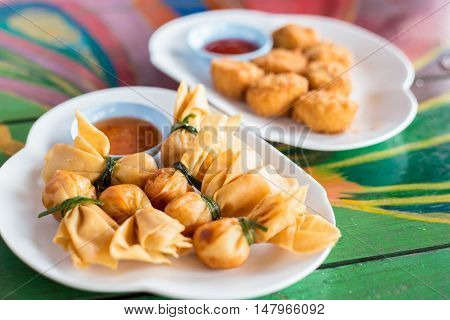 Deep fried shrimp dumplings with sauce on a colored wooden table in Thailand