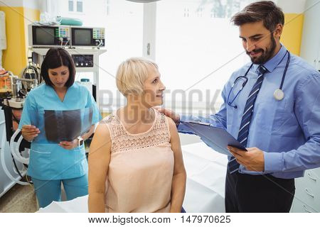 Male doctor interacting with a patient while nurse looking at x-ray in the hospital