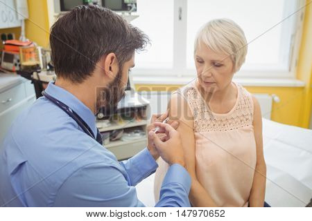 Male doctor giving an injection to a patient at the hospital