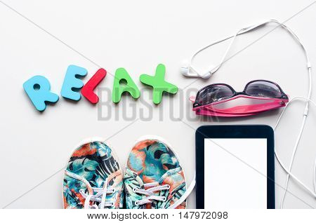 colorful canvas shoe and sunglasses with RELAX alphabet on the floor ground background. accessories for travelling