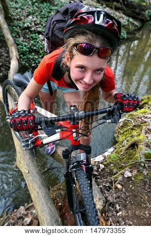 Bikes cycling girl. Girl rides bicycle. Girl cycling fording throught water . Cycling trip is good for health. Cyclist look in camera. River on background.