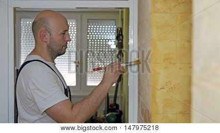 House Painter Working.  Home Renovation. Portrait Of A Man Painting A Wall With Paint Brash.