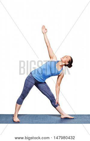 Beautiful sporty fit woman practices yoga asana utthita trikonasana - extended triangle pose beginner variation isolated on white