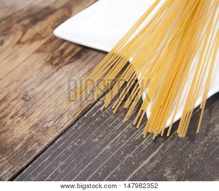 Pile of spelt spaghetti on white platen on wooden table