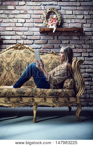 Young blonde woman resting on baroque style sofa in stylish home, using tablet computer. Side view.