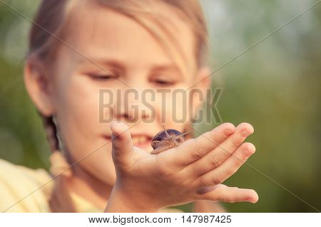 Happy little girl playing in the park with snail at the day time. She having fun on the garden. Concept of the kid is ready to go to school.