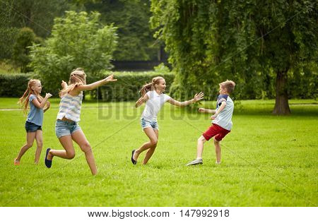 friendship, childhood, leisure and people concept - group of happy kids or friends playing catch-up game and running in summer park