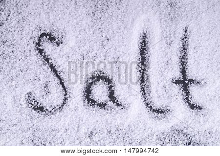 Letters Salt On The Salt Crystals On A Black Background. The Letters On The Salt.