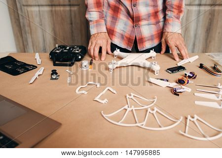 Disassembled drone on table. Unrecognizable person near table with elements for quadrocopter building. Modern technologies, innovation, hobby, aeromodelling concept poster