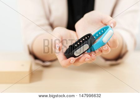 Activity trackers presentation, close-up. Female hands holding blue and black fitness bracelets. Sport, active and healthy lifestyle, modern technologies concept
