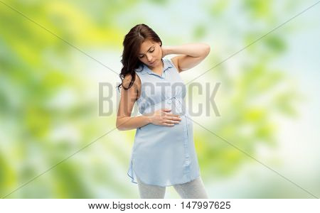 pregnancy, health, people and expectation concept - pregnant woman touching her neck and suffering from ache over green natural background