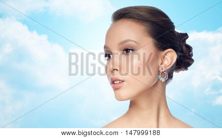beauty, jewelry, accessories, people and luxury concept - close up of beautiful asian woman face with earring over blue sky and clouds background