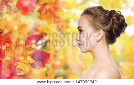 health, people and beauty concept - beautiful young woman face over natural autumn leaves and lights background