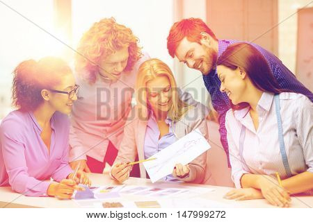 business, office, clothes design and starup concept - smiling creative team looking at sketch