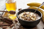 oatmeal porridge with banana nuts honey and spices in ceramic bowl with a spoon. healthy breakfast. top view poster