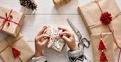 Woman's hands wrapping christmas holiday handmade present in craft paper with twine ribbon. Making bow at xmas gift box, decorated with snowflake. Scissors on white wooden table, top view. poster