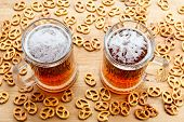 Mug of cold foamy beer with brezel. Overhead view. Traditional german Oktoberfest snacks and beer on wooden background poster