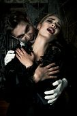 Bloodthirsty male vampire in medieval dress is biting a beautiful lady. Halloween.  poster