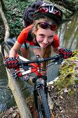 Bikes cycling girl. Girl rides bicycle. Girl cycling fording throught water . Cycling trip is good for health. Cyclist look in camera. River on background. poster
