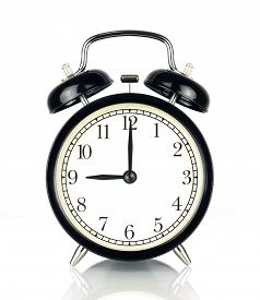 Alarm Clock isolated on white in black and white showing nine o'clock.