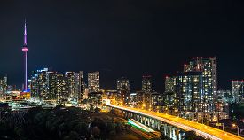 Glowing light streaks from Gardiner Expressway as traffic  never stops.  Hot & muggy summer night in Lakeside  Toronto, Canada.