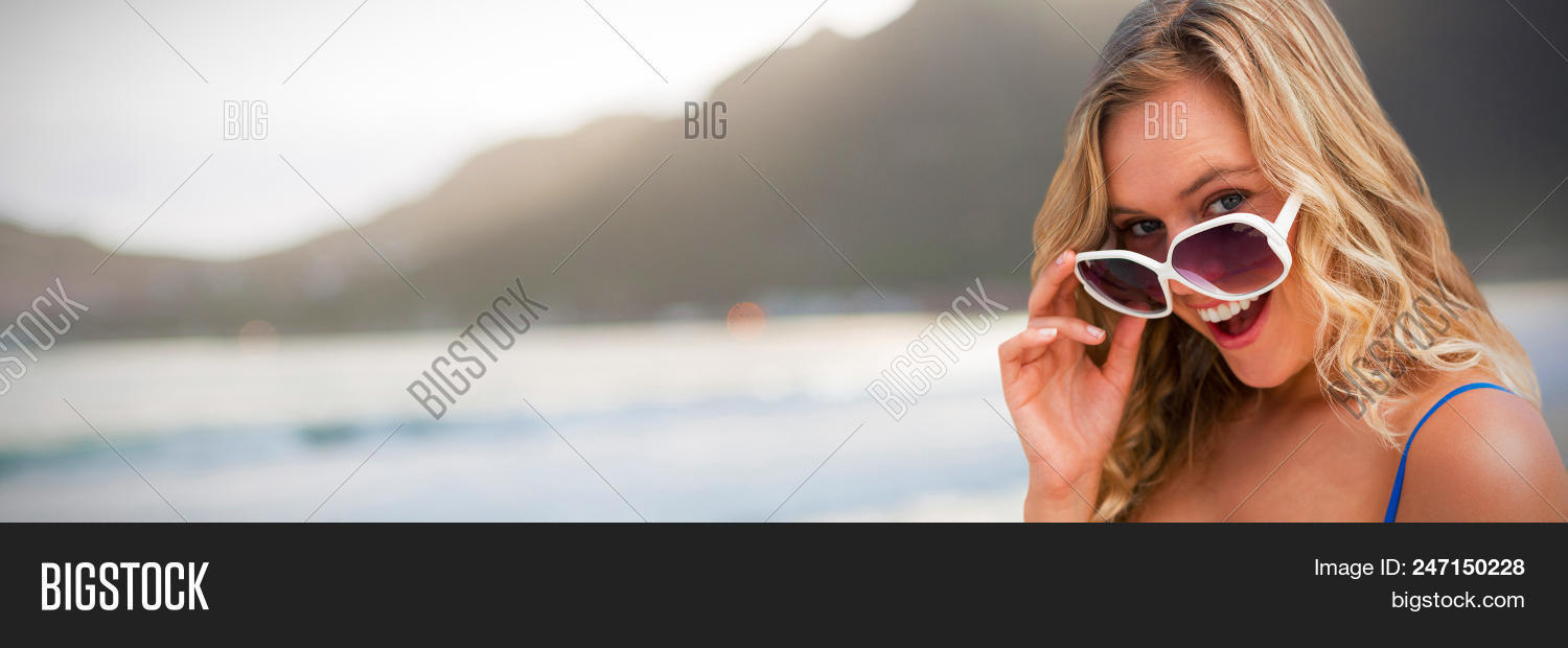 e40e83dbd1 Portrait of young women wearing sunglasses against mountain against sky at  beach