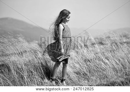Child In Nature. Little Cute Brunette Girl In Blue Lace Summer Dress Looking Away Standing In Mounta