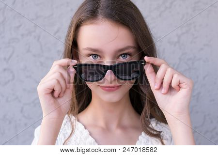 Close-up Portrait Of Young Attractive Female With Beautiful Sky-blue Eyes In Sunglasses And Closely