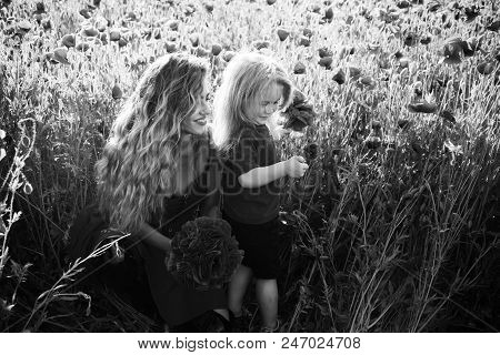 Family Holiday. Woman And Happy Little Boy Child With Long Curly Hair Hold Flower Bouquet In Field O