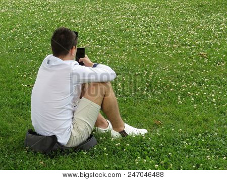 Young Man Sitting On The Grass With A Smartphone In A Clover Lawn. Summer Male Fashion, Mobile Commu