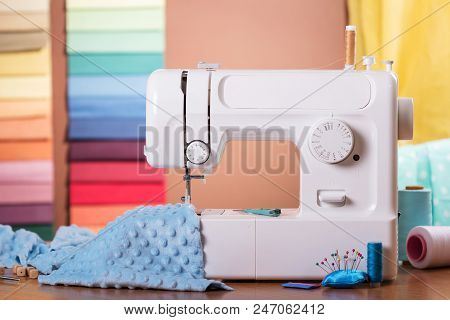 Sewing Machine And Cloth In Work, Sewing Supplies On Wooden Table