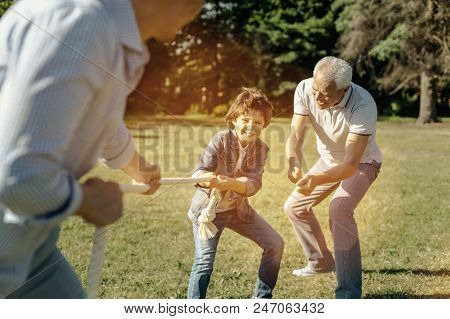 Determined To Win. Happy Smiling Vigorous Boy Playing Rope-pulling With His Dad And Bending Down Whi