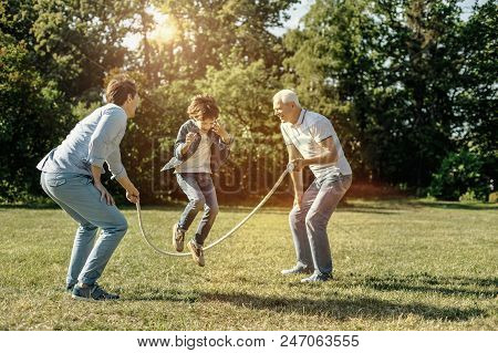 Feeling Energetic. Vigorous Happy Laughing Boy Jumping Rope While His Dad And Grandfather Holding It