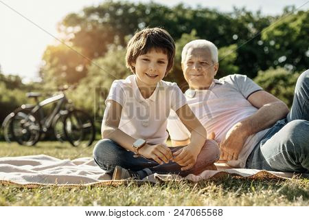 Sunny Weather. Happy Vigorous Smiling Boy Relaxing And Sitting On The Grass With His Grandpa Looking