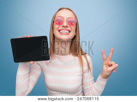 Cheerful Blond Woman In Pink Sunglasses Showing Two Fingers And New Touchpad Smiling At Camera On Bl