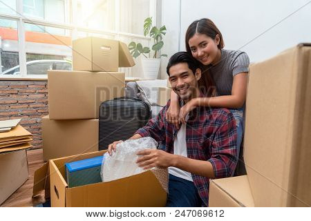 Asian Young Couple Packing Into Big Cardboard Box For Moving In New House, Sitting On Difference Ste