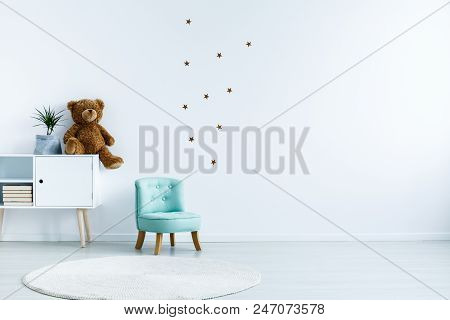Small Light Blue Armchair For Kid Standing In White Room Interior With Stars On The Wall, White Rug