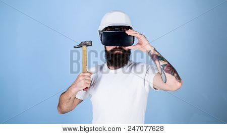 Hipster On Serious Face Wear Helmet, Hold Hammer In Virtual Reality. Virtual Renovation Concept. Man