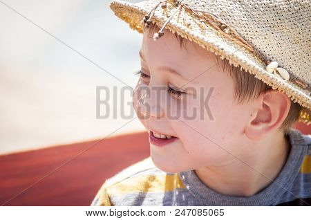 Cute Caucasian Kindergarten Age Child In A Straw Hat Outside In The Summer Heat. Time Together With