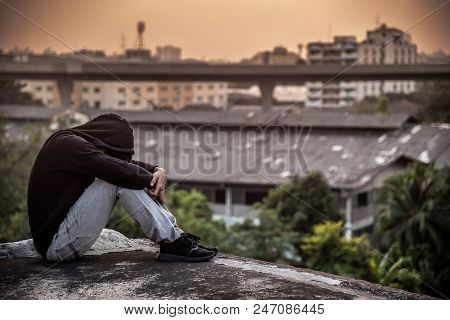 Young Asian Man Sitting On Rooftop Of Abandoned Building With Depression Stress Out During Sunset Ti