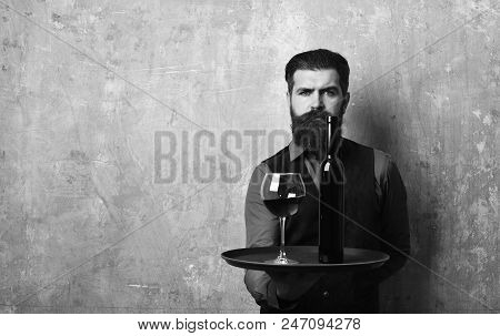 Waiter With Glass And Bottle Of Red Wine On Tray.. Man With Beard Holds Wine On Beige Wall Backgroun