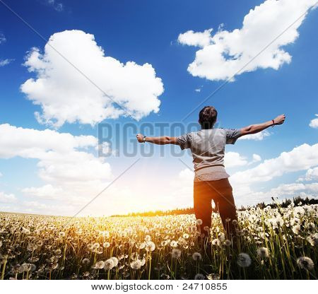 Young man with raised hands standing on a meadow with dandelions