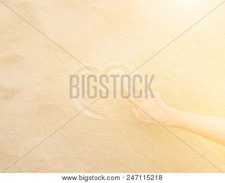 Young Caucasian Woman Draws With Hand Heart On Fine White Beach Sand By Ocean