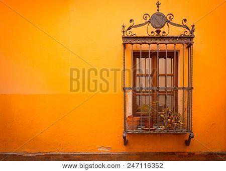 Antique Medieval Window With Rusty Iron Bars And Russet Orange Orange Wall In Old Santa Cruz Quarter