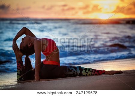 Sunset Meditation. Young Active Woman Stretching In Yoga Pose On Sea Beach To Keep Fit And Health. H