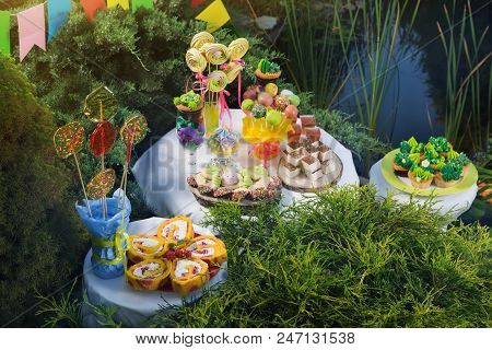 on three dessert tables a large assortment of muffins and chocolates, a candy bar for a birthday, a children's holiday outdoors poster