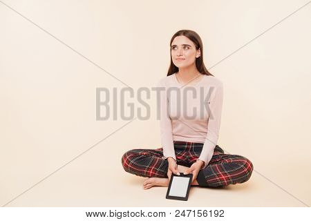 Pretty young brunette girl dressed in pajamas holding ebook while sitting with legs crossed and looking at copy space isolated over pink background