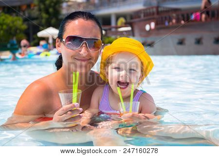 Mom with little daughter drinking juice at the pool on summer holidays