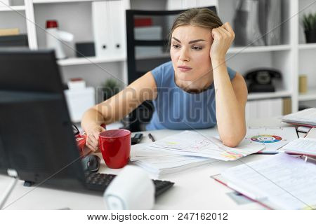 Beautiful Young Girl In A Blue Dress Is Working In The Office. Photo With Depth Of Field