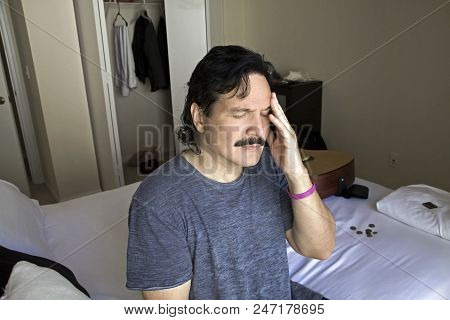 Hispanic Man With Fingers Touching His Temple In A Sign Or Pain Or Discomfort.